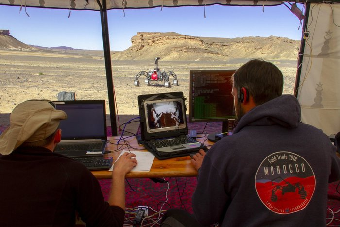 Engineers watch the progress of one of the test rovers in Morocco.