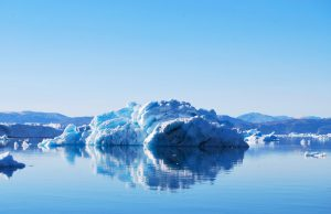 Blue-white snow and ice next to water.