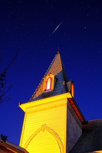 A church steeple in the foreground, with an iridium flare in the sky behind it.