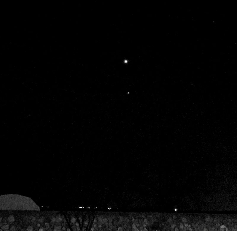 Two small round lights in a black sky seen over the top of a gray stone wall.