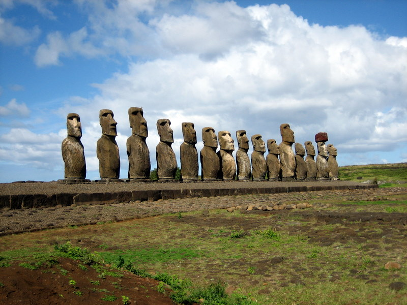Fifteen huge monolithic stone statues of partial human figures with big heads lined up against blue sky.