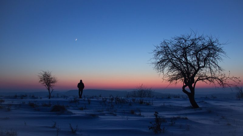 snowy landscape, clear sky, silhouette of man looking at sliver of young crescent moon