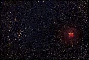 Field of stars with a star cluster on one side, plus the red moon in eclipse