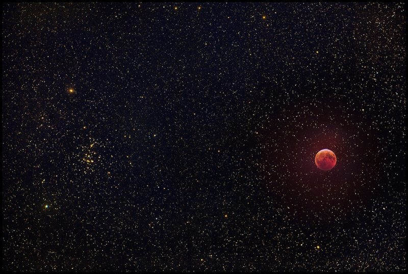 Field of stars with a star cluster on one side, plus the red moon in eclipse.