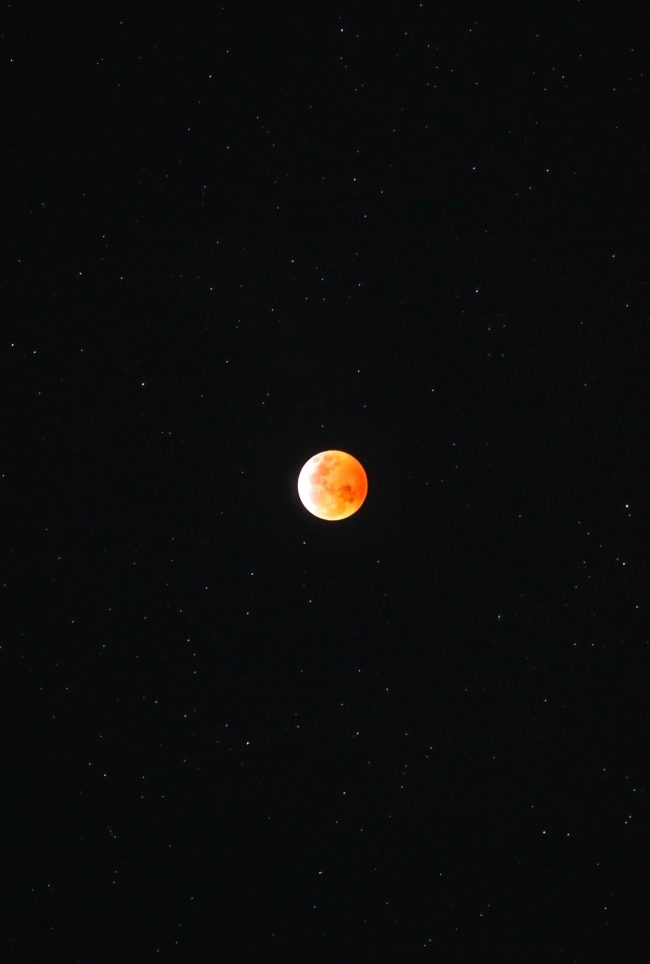 Bright orange eclipsed moon, on black background, with scattered stars.