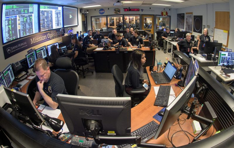 tense-looking scientists sitting in control center room