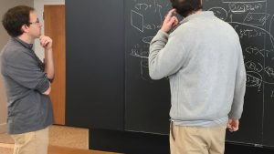 Two physicists looking at a blackboard covered with equations