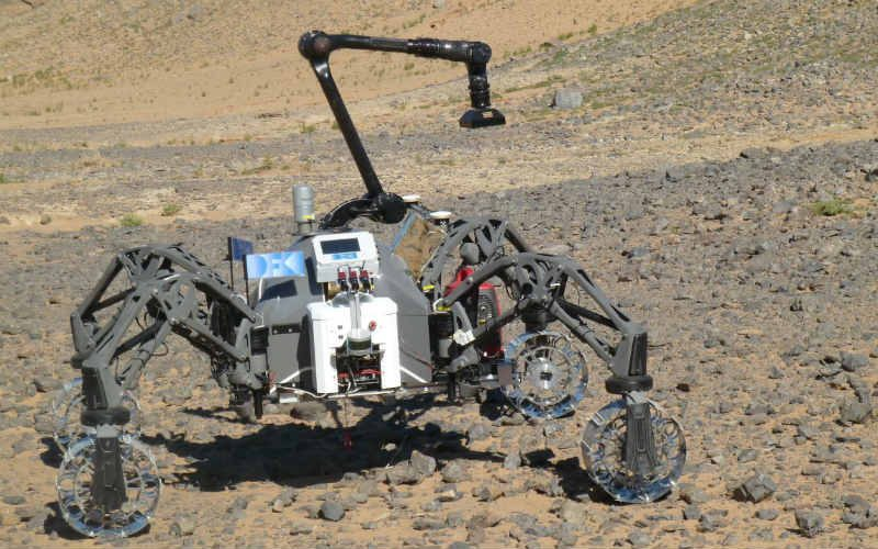 view from above of the spidery four-wheeled rover showing a large robotic arm
