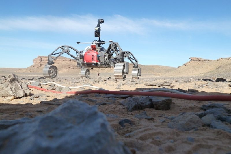 spider-like four-wheeled rover on a rocky landscape