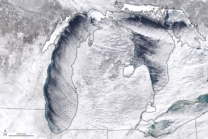 White and gray satellite view of Great Lake area, lines of clouds over lakes, land all white.