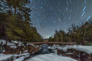 dark sky with star trails over snowy, rocky, river.