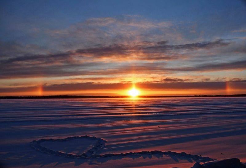 A lake beach with a heart stamped into snow, with a sunrise and sun halo over the lake.