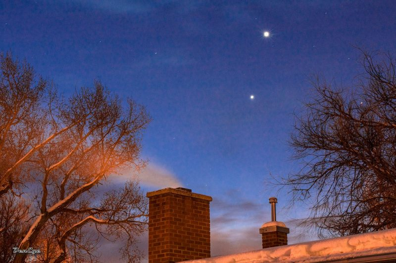 In the foreground, a chimney with smoke. Behind, in a twilight sky, 2 bright dots, Venus and Jupiter.