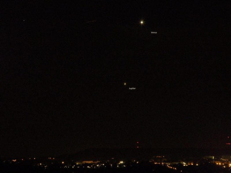 Black background with 2 bright dots, Venus and Jupiter, above town lights.