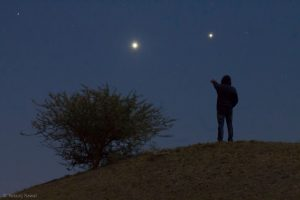 Venus, brighter, and Jupiter, fainter, with a tree and a human in the foreground.