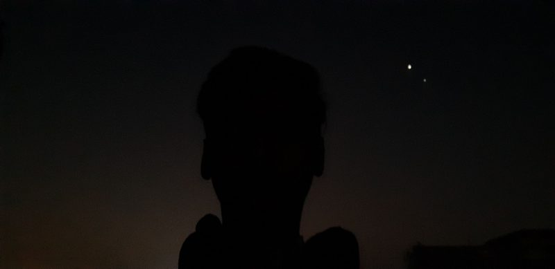 Silhouette of human head with two bright dots beside it.