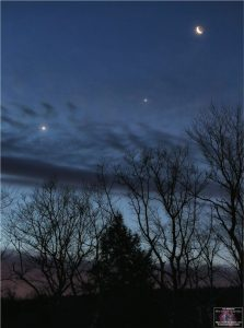 Dawn breaking, with a line of objects in the east, moon highest, Jupiter next, then Venus.