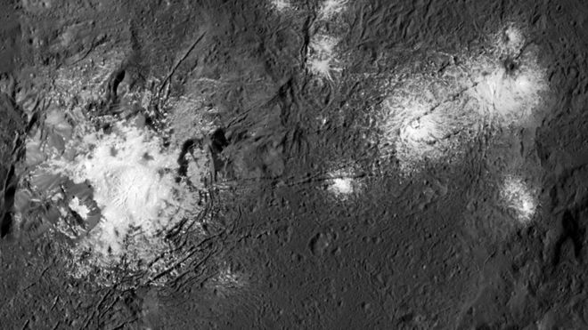 Bright white spots on rocky surface, brighter in the middle and fuzzy around the edges.
