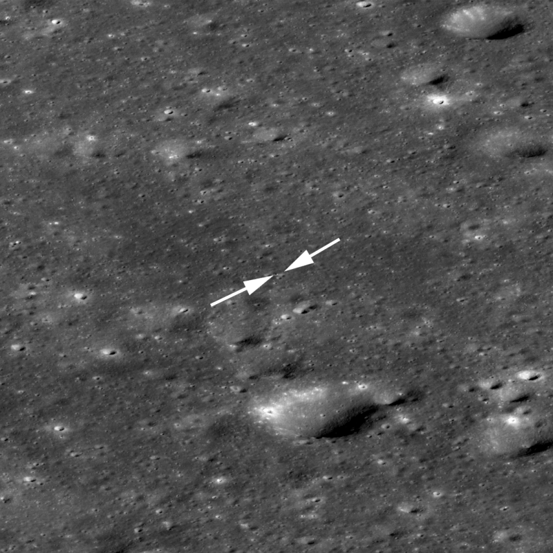 Wider view of cratered gray surface with arrows pointing to bright white dot.