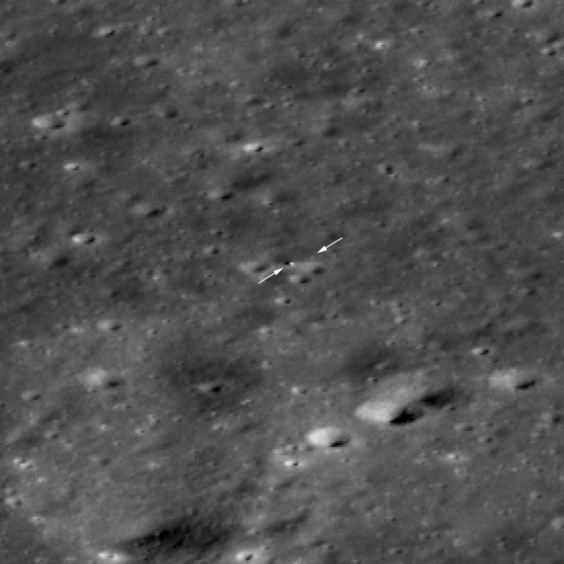Slightly blurry closeup of surface with arrows pointing to 2 tiny white dots.