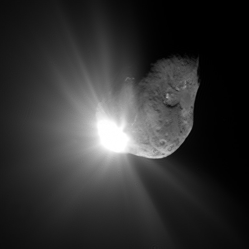A large irregular cratered space rock with a bright spot on one side with rays of light coming from it.