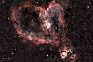 Pink stars in the shape of blobby heart in a dark sky