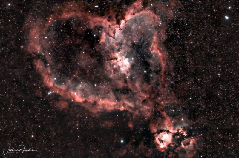 Pink stars and cloudy pink outline in the shape of blobby heart in a dark sky.