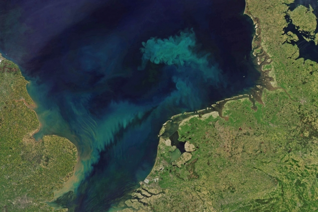 Coastline viewed from space with bright blue and green streaks and splotches in the ocean.