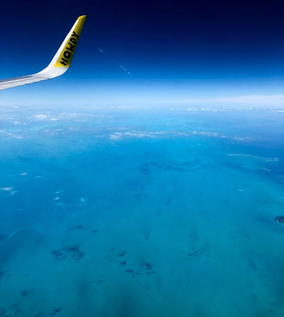 Smoke trail behind aircraft tail over bright blue sea.