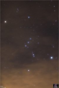 Constellation Orion through thin yellowish clouds.