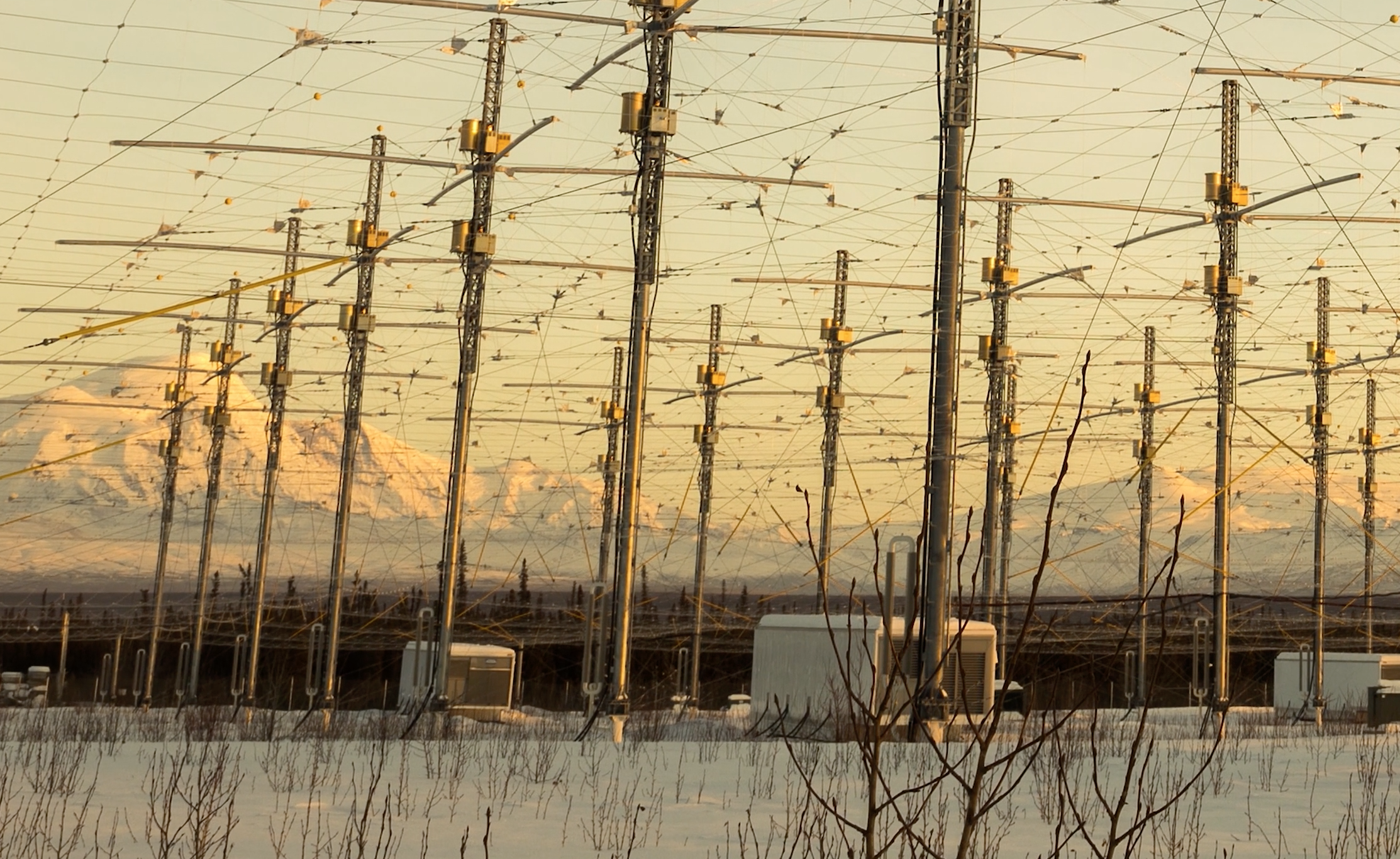 Yellow sky, wires and poles, snow on the ground, snowy mountains in distance.