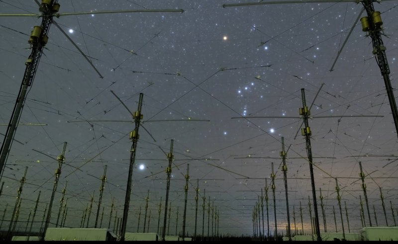 Starry sky with wires and poles. Orion very bright behind wide antennas.