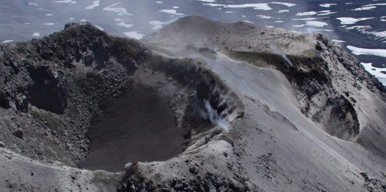 Aerial view of crater with water in it on an ash-covered mountain top.