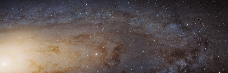 Bright galactic center to left, part view of spiral arms with stars and dust lanes to right.
