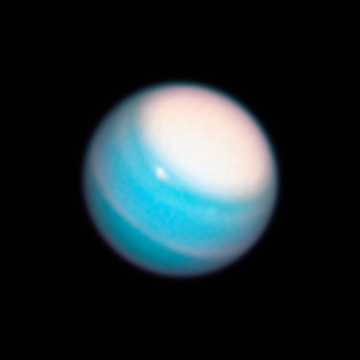Large, bright cloud cap over north pole of blue planet Uranus.