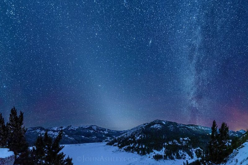 Starry sky, with a cone-shaped light emanating from a snowy mountain horizon.