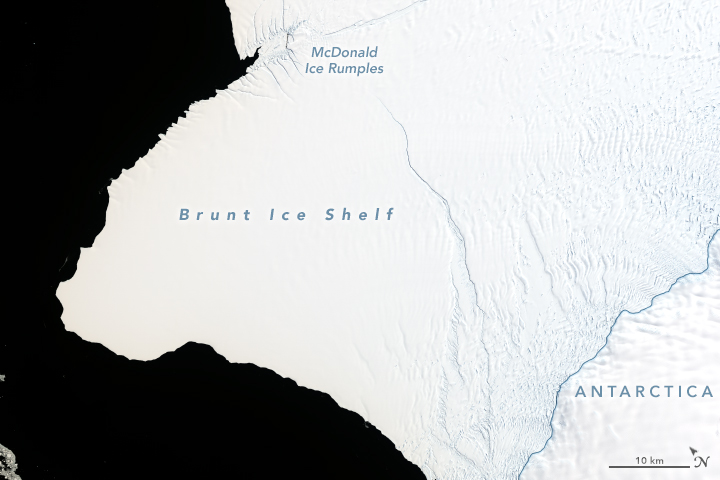 Large, white area (ice) against black ocean with long crack across it.