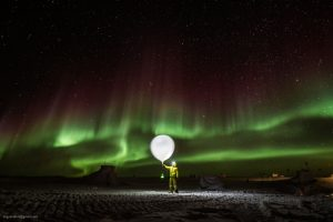Green aurora in background. Man in foreground is holding up a man-sized balloon!