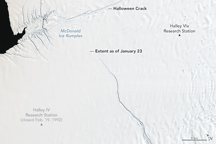 Close-up orbital view of ice shelf with large crack across it.