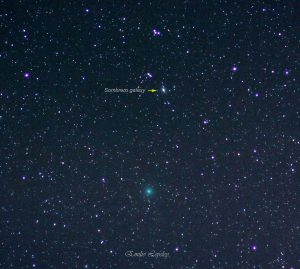 A rich star field, with the green comet below and tiny Sombrero Galaxy above.