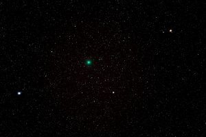 A greenish fuzzy comet against a star field.