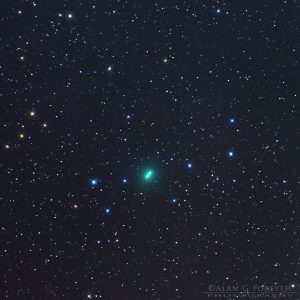 Green comet - blurred due to movement - in front of starry background.