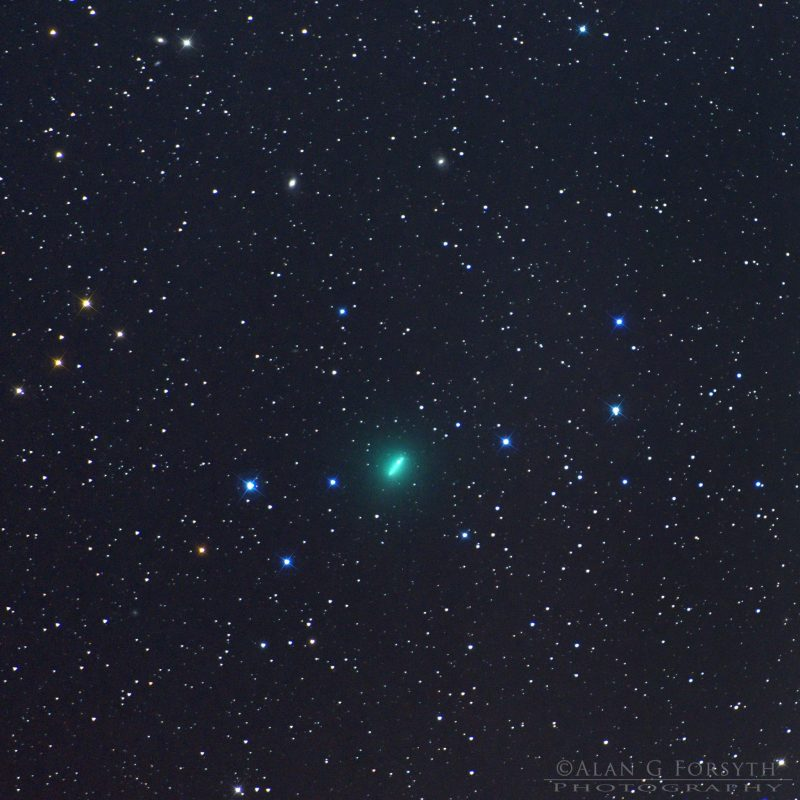 Green comet, elongated due to movement, in front of starry background.