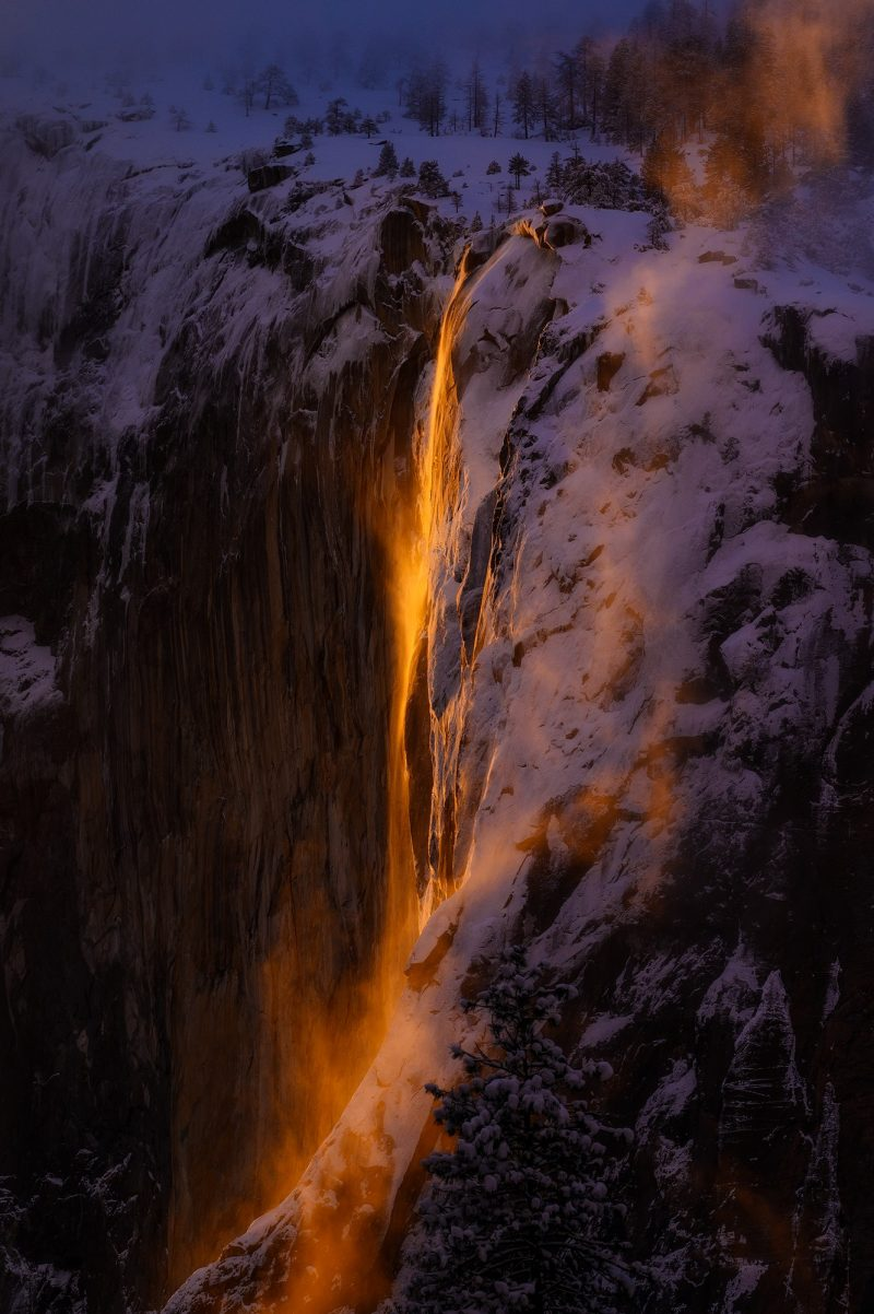 Tall, thin waterfall on rocky cliff lit by an orange glow.