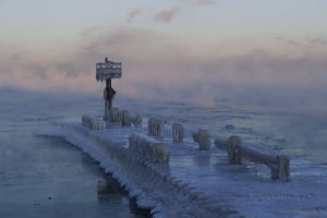Pier and water covered in blue-white ice.