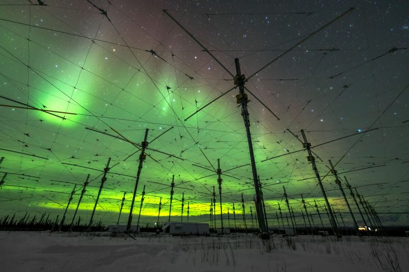 Florescent green aurora. Sky criss-crossed with wires and telephone poles.