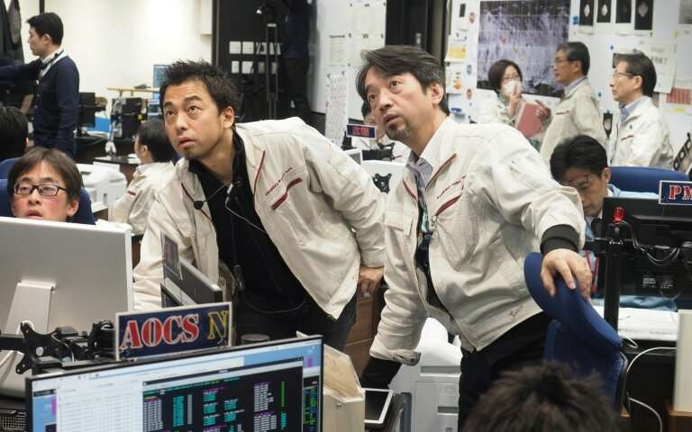 White-jacketed scientists in a control room, looking anxious.