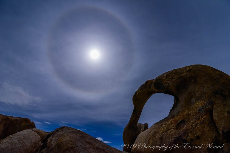 Moon with halo over twisted-looking large rock arch.