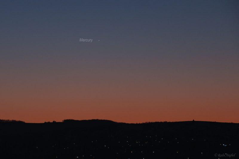 Twilight sky with glow along dark horizon and small, dim dot above.