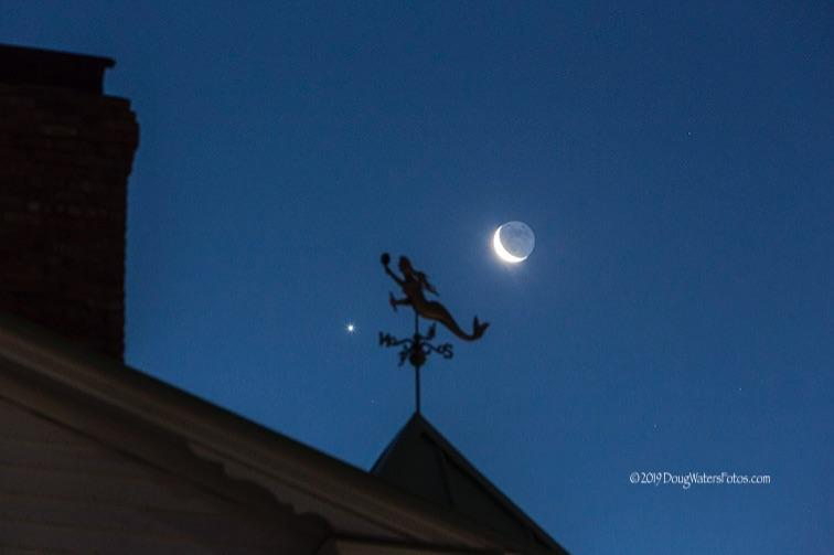 Venus and moon on each side of a mermaid-shaped weathervane.